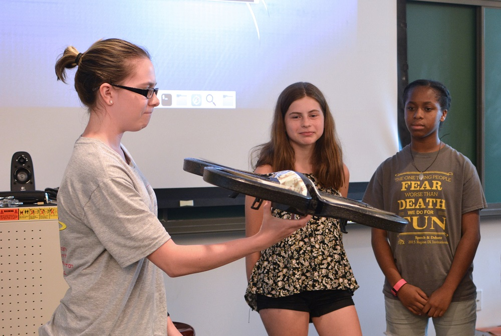 Students at science summer camp with drone