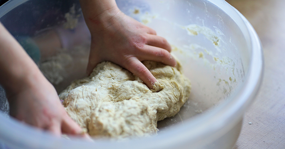 Photo of a pizza maker kneading the dough