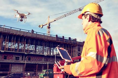 worker flies drone on construction site