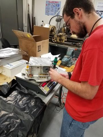 Photo of a Project Aether team member working on a satellite payload